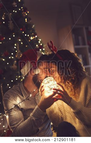 Beautiful couple in love sitting on the living room floor next to a Christmas tree holding a jar with Christmas lights