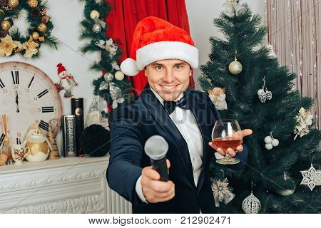 smiling man with a phicrophone and a glass of whiskey in his hands on a New Year's background.