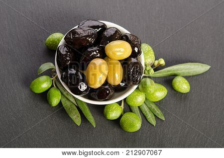 Black And Green  Olives  Mixed In The  Porcelain Bowl On Gray Stone