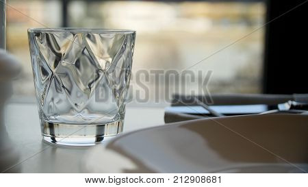 Faceted glass of water on nature background. Clear faceted glass with whiskey on a dark wooden table, close-up. Empty faceted glass 4K
