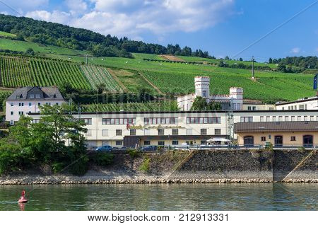Panoramic view of the Asbach Confiserie (confectionery) with Rottland castle, the vineyards, and the floating cable cars in the background. Rudesheim am Rhein, Germany - August 1st 2015.