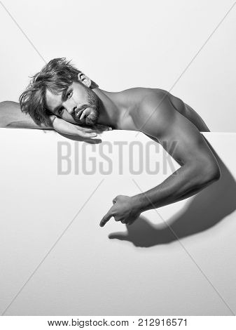 Handsome serious guy sexy young bearded macho man model with bare muscular chest and hands on white background copy space