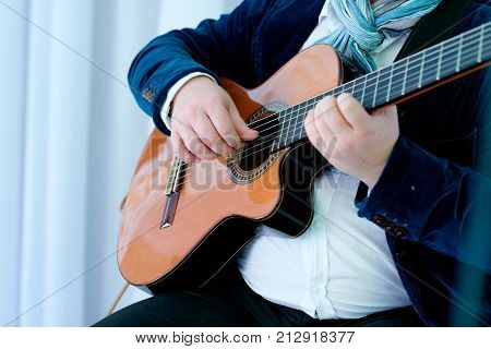Hands playing acoustic guitar jazz, close up