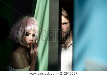 Conflict unhappy love. Couple of woman and man separated by green blue wall. Crisis relationship divorce. Girl wear pink wig and macho with beard. Separation split concept.