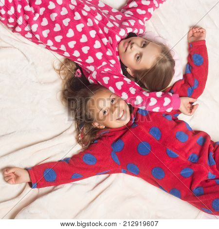 Comfort home concept. Girl sisters in pajamas happy smile in bed top view. Children nightwear fashion. Bedtime slumber dream sleepover. Childhood family love friendship.