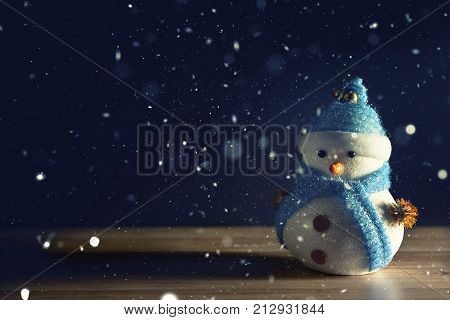 Happy snowman standing in dark winter christmas snow background. Merry christmas and happy new year greeting card with copy-space. Christmas celebration holiday background.