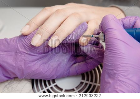 Master removes shellac gel nails which are exfoliated with sawing tool. Concept manicure.