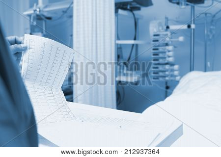 Male doctor checks up the ECG next to the patient's bed at the night duty.