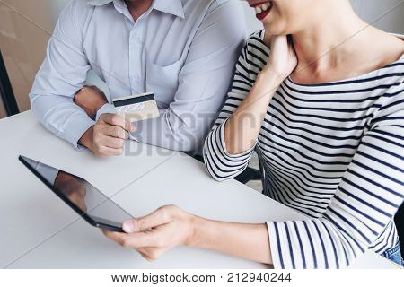 Two people using tablet and credit, debit card register payments online shopping and customer service network connection market using technology on global Internet Online shopping or banking concept.