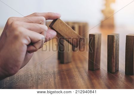 Risk and strategy in business Close up of businessman hand gambling placing wooden block on a line of domino.