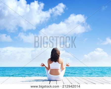 Attractive woman in white sporty clothes doing yoga on a wooden pier. Yoga, sport, leisure, recreation and freedom concept.
