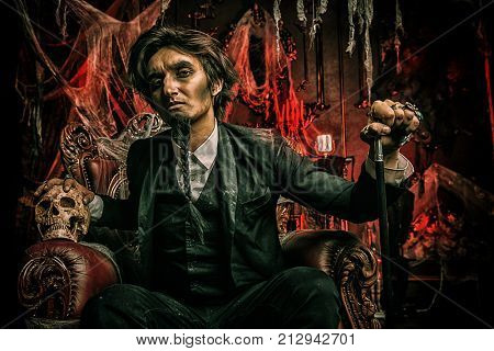 Halloween. Frightening gloomy man in a black tailcoat sits in an armchair with a skull in an old abandoned castle. The Dark Lord. Vampire man.
