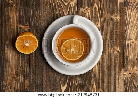 Hot beverage with sugar cubes on wooden background. Cup of green tea with slice of orange fruit. English tea time concept. Tea cup with citrus slices making cozy composition top view.
