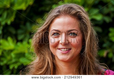 Confident and smiling beautiful Caucasian girl with curly hair.