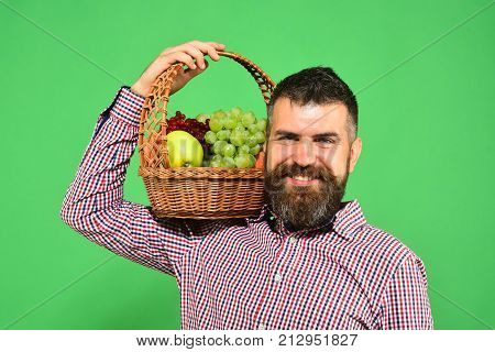 Man With Beard Holds Basket With Fruit On Shoulder