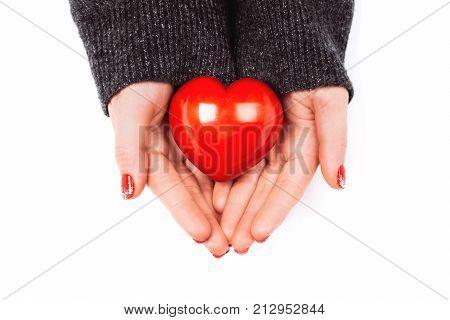 Woman's hands with beautiful accurate manicure carefully keep red heart. Concept of giving help to them, who needs.
