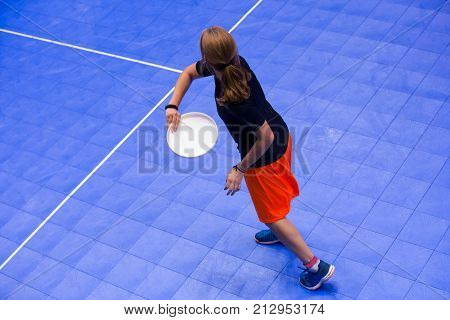 A girl on a sports ground throws flying disc. Sport hall. Girl with long hairs throwing a disc.