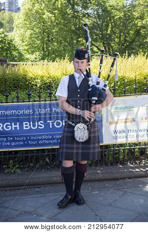 EDINBURGH SCOTLAND - May 26th 2017: Edinburgh street bagpiper at Nor Loch Edinburgh Scotland May 26 2017. The bagpipe players are a major tourist attraction in Scotland.