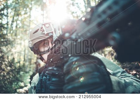 Image of military man in helmet and with submachine gun on task in forest. Lensflare effect