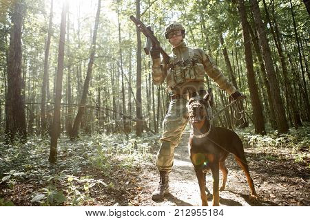 Photo of military man with dog and submachine gun in forest on reconnaissance