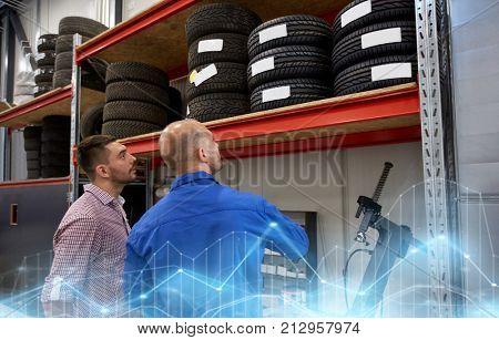 auto service, repair, maintenance and people concept - mechanic and man looking at tires at car shop