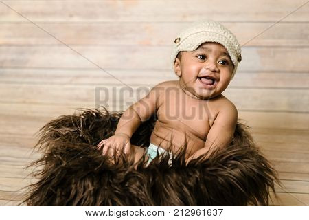 Infant mixed race healthy looking baby boy wearing knitted hat sitting in a fluffy furry basket wooden background modern studio shoot vintage look smiling happy six months old having fun