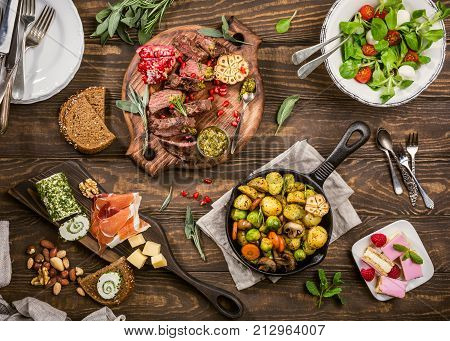 Flat lay of delicious dinner table with roasted meat steak, appetizers and desserts. Top view. Healthy food concept.