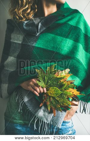 Woman in warm woolen green check scarf or blanket and blue jeans with Autumn fallen leaves in her hands. Fall cosy mood lifestyle concept