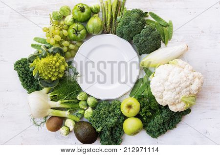 Above view of green vegetables and fruits arranged in a circle frame, copy space for text in the middle, selective focus