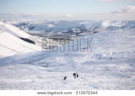 PEAK DISTRICT UK - CIRCA 2012: A group of people hiking on Kinder Scout in winter with Edale valley in the distance. Peak District UK