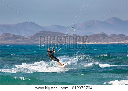 FUERTEVENTURA SPAIN - CIRCA 2013: A middle aged man kite surfs off the coast of Corralejo in the Canary Island of Fuerteventura. Lanzarote is visible in the background beyond Isla de Lobos