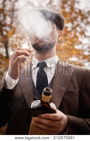 Gangster in a good suit, a cap smokes and holds a cigarette and a bottle of whiskey