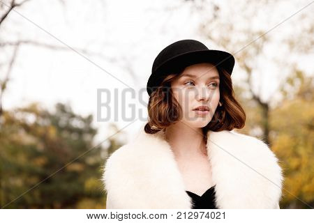 A beautiful girl in retro clothes in a black hat, a fur coat white on a blurred background of an autumn park