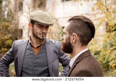 Two young gangsters in good suits discuss business in a deserted place on a blurred background