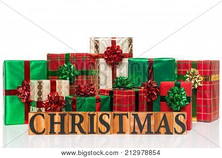 The word Christmas in wooden letters in front of gift wrapped presents, cut out on a white background.