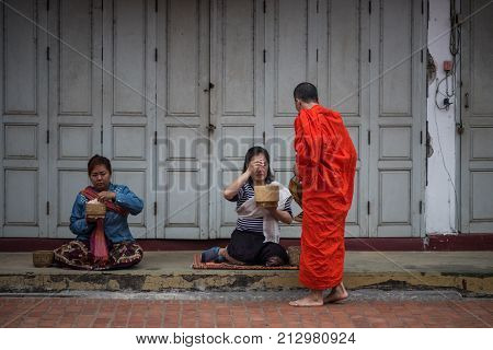 Luang Prabang, Laos - December 21, 2015: A monk is walking to collect alms and offerings in the world heritage site, Luang Prabang, Laos.