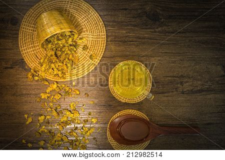 Chrysanthemum tea and honey bee on wood background Extend the arteries at the heart. Help prevent artery diseases such as hypertension angina.It absorbs carcinogens and microorganisms.
