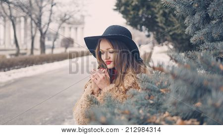Young attractive girl outdoors in winter. She is wearing a wide-brimmed hat and a fur coat. The girl is standing next to the fir-tree. She's warming her hands