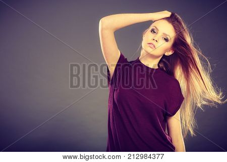 Haircare beauty hairstyling concept. Portrait of young attractive brunette woman wearing dark tshirt having windblown beautiful long brown hair.