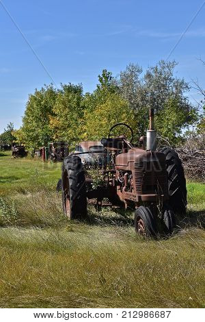 An old rusty tractor is left out in a pasture with other discarded farm equipment and cars.