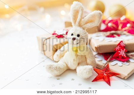 Christmas and New Year background with toy plush rabbit presents and decorations for Christmas tree. Holiday background with stars confetti and light bulbs. Place for text. poster