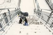 boy shoveling snow from the stairs. child cleans the stairway overpass after snowfall. view from above. the concept of selfless assistance, citizen responsibility poster