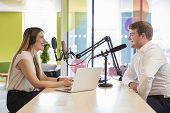Young woman interviewing a guest in a studio for a podcast poster