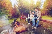 camping, travel, tourism and hike concept - happy family sitting on bench and talking at camp near campfire in woods poster