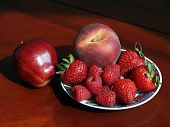 Strawberries, raspberries, peach and apple are on the plate on mahogany table poster