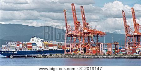 Container Ship Unloads In The Port Of Vancouver, Red Sea Cranes And Colorful Containers On The Backg