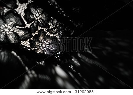 Abstract Background Of Shadows Black Floral Laces On White Table. Light Going Through Black Lace. Ro