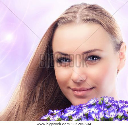 Beautiful female holding flowers, girl face with bouquet of spring plant, bunch of purple cornflowers, lovely woman with gift over pink abstract background