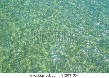 Clear Water Green And Small Waves With Reflections From The Sun, Suitable For Background Images.