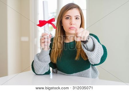 Beautiful young woman holding degree with red bow pointing with finger to the camera and to you, hand sign, positive and confident gesture from the front